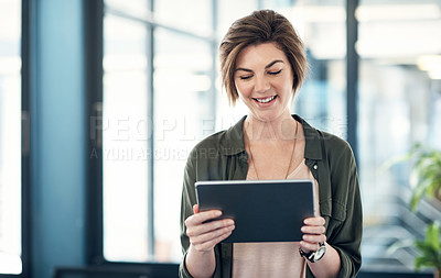 Buy stock photo Shot of an attractive young businesswoman using a digital tablet in an office