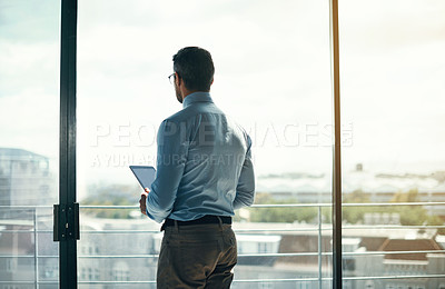 Buy stock photo Rearview shot of a mature businessman looking out the window in an office