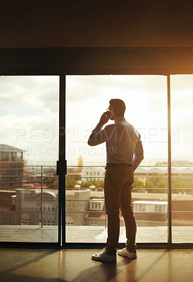 Buy stock photo Silhouette of a mature businessman standing in front of an office window and using a mobile phone