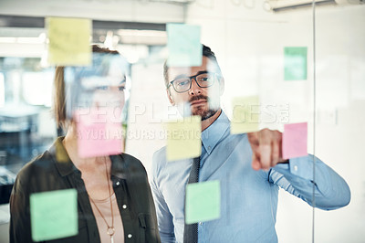Buy stock photo Shot of a businessman and businesswoman having a brainstorming session in a modern office
