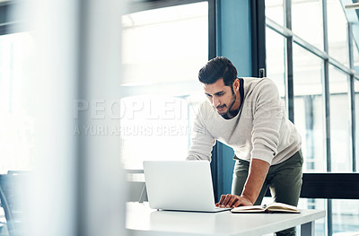 Buy stock photo Shot of a young businessman using a laptop at his desk in a modern office