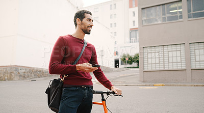 Buy stock photo Cropped shot of a handsome young man using a cellphone and walking with his bicycle in the city