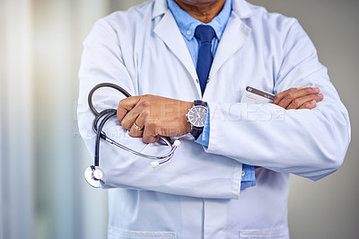 Buy stock photo Shot of an unrecognizable male doctor standing with his arms folded inside of a hospital during the day