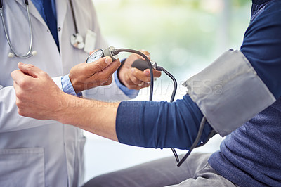 Buy stock photo Shot of an unrecognizable male doctor checking the blood pressure of a patient while being seated inside of a hospital during the day