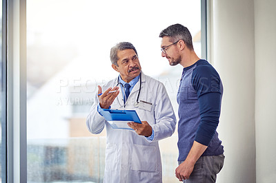 Buy stock photo Shot of a confident mature male doctor consulting a patient while standing inside a hospital during the day