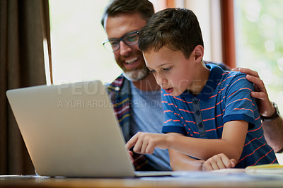Buy stock photo Cropped shot of a mature father and his adorable son using a laptop together at home
