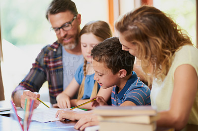 Buy stock photo Cropped shot of two parents helping their adorable children with schoolwork at home