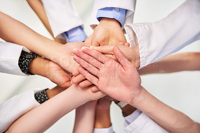 Buy stock photo Low angle shot of a group of medical practitioners joining their hands together in a huddle
