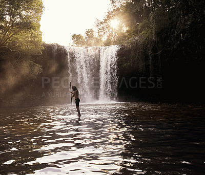 Buy stock photo Shot of a young man paddle boarding on a lake
