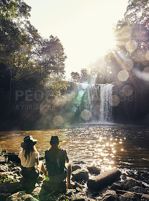 Buy stock photo Shot of a young couple admiring the view of a waterfall over a lake