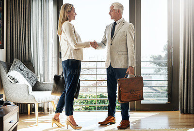 Buy stock photo Shot of two confident businesspeople shaking hands in agreement inside a house during the day