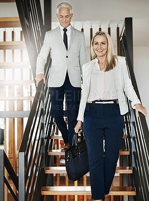 Buy stock photo Portrait of two confident businesspeople walking down stairs together while talking inside a building during the day