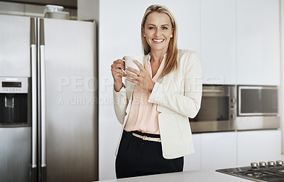 Buy stock photo Portrait of a cheerful middle aged businesswoman standing behind a counter while drinking a cup of coffee inside of a kitchen during the day