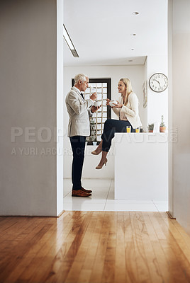 Buy stock photo Shot of a cheerful mature couple eating breakfast cereal together in the kitchen at home during the day