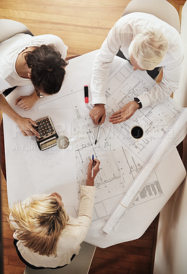 Buy stock photo High angle shot of a group of architects working together on blueprints of a house around a table inside of a building