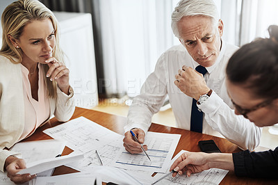 Buy stock photo Shot of a group of architects working together on blueprints of a house around a table inside of a building