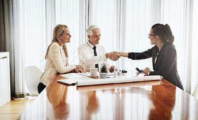 Buy stock photo Shot of a group of architects working together on blueprints of a house around a table while shaking hands in agreement inside of a building