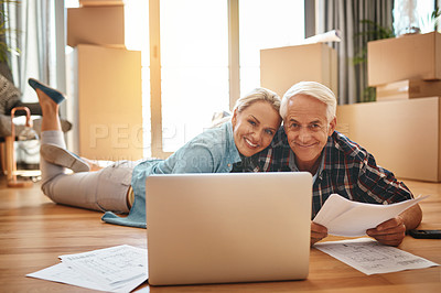 Buy stock photo Portrait of a mature couple using a laptop and going through paperwork together on moving day