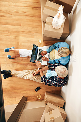 Buy stock photo High angle shot of a mature couple using a laptop together on moving day
