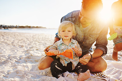 Buy stock photo Shot of a father building sandcastles with his little son at the beach
