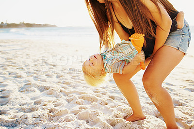 Buy stock photo Shot of a mother bonding with her little son at the beach