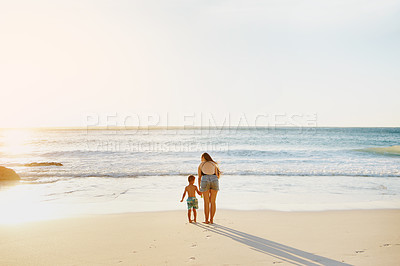 Buy stock photo Rearview shot of a mother and her little son walking together along the beach