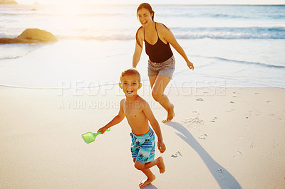 Buy stock photo Shot of a mother playing with her little son at the beach
