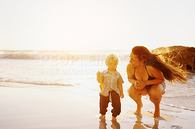 Buy stock photo Shot of a young woman and her adorable son playing together at the beach