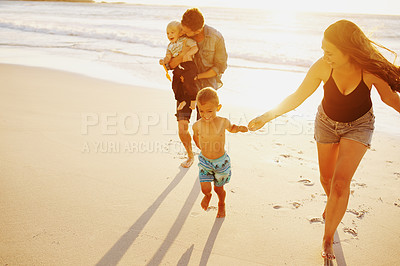 Buy stock photo Shot of a happy young family having a fun day at the beach