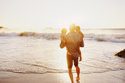 Buy stock photo Rearview shot of a young man carrying his sons while going for a walk on the beach