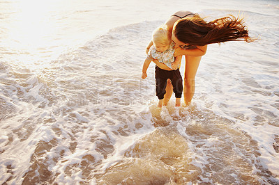 Buy stock photo Shot of a young woman and her adorable son having fun at the beach