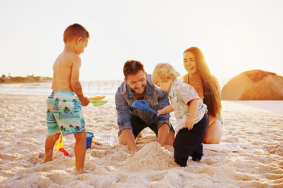 Buy stock photo Shot of a happy young family building sandcastles together at the beach