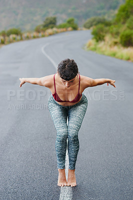 Buy stock photo Shot of a young woman practicing yoga outdoors