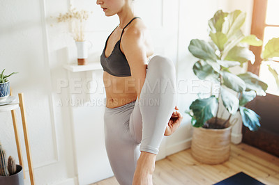 Buy stock photo Shot of an unrecognizable woman doing yoga at home