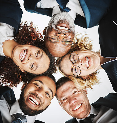 Buy stock photo Low angle portrait of a group of businesspeople huddled together in solidarity
