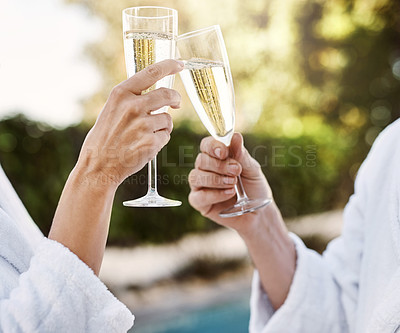 Buy stock photo Shot of two unrecognizable people having a celebratory toast with champagne outside during the day