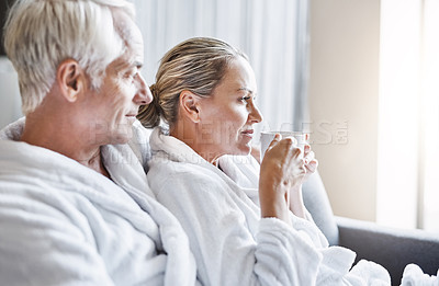 Buy stock photo Shot of a cheerful middle aged couple relaxing together while wearing bathrobes and sitting on a couch inside of a spa during the day