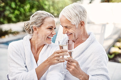 Buy stock photo Shot of a cheerful middle aged couple having a celebratory toast with champagne outside during the day