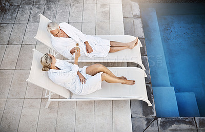 Buy stock photo High angle shot of a cheerful middle aged couple relaxing in bathrobes next to a swimming pool at a spa outside during the day