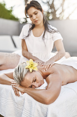 Buy stock photo Shot of a relaxed middle aged woman lying on her stomach while receiving a massage at a spa outside during the day