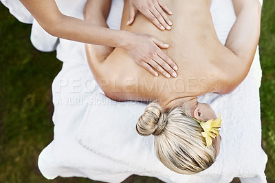 Buy stock photo High angle shot of a relaxed middle aged woman lying on her stomach while receiving a massage at a spa outside during the day