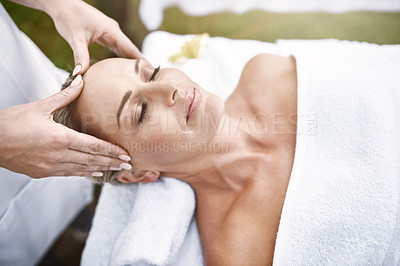 Buy stock photo Shot of a relaxed middle aged woman lying on her back while receiving a massage at a spa outside during the day
