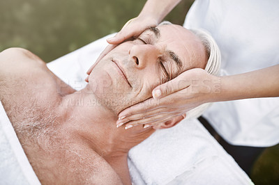 Buy stock photo Shot of a relaxed middle aged man lying on his back while receiving a massage at a spa outside during the day
