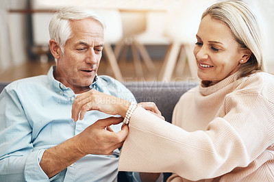 Buy stock photo Cropped shot of mature man giving his wife a gift on the sofa at home