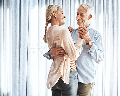 Buy stock photo Cropped shot of an affectionate mature couple dancing in their home