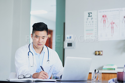 Buy stock photo Cropped shot of a young male doctor making notes while working in a hospital
