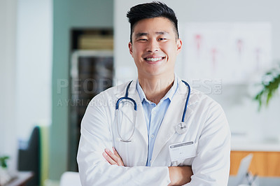 Buy stock photo Cropped portrait of a young male doctor standing with his arms folded in a hospital