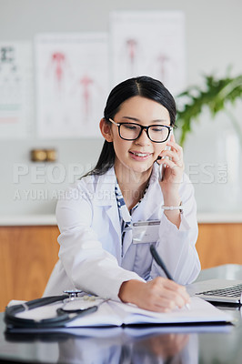 Buy stock photo Cropped shot of a young female doctor making notes while working in a hospital