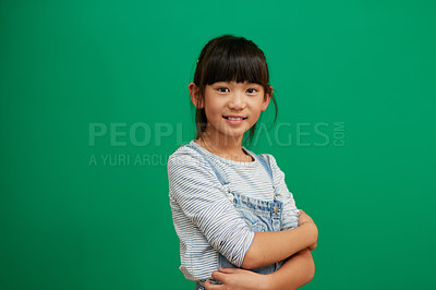 Buy stock photo Studio portrait of confident little girl standing with her arms folded against a green background