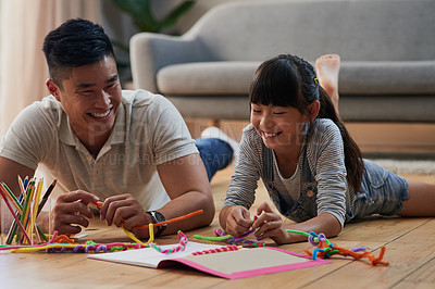 Buy stock photo Shot of a cheerful father and daughter doing homework together while lying on the floor at home during the day